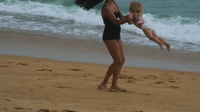 Mother turns her little girl on arms and sandy beach stock video footage