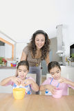 Mother and Twins Beating Eggs in Kitchen Royalty Free Stock Photos