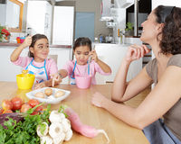Mother and Twins Beating Eggs in Kitchen Royalty Free Stock Image