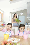Mother and Twins Beating Eggs in Kitchen Stock Image