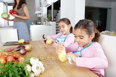 Mother and Twins Peeling Potatoes in Kitchen Stock Photos
