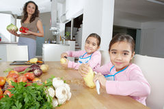Mother and Twins Peeling Potatoes in Kitchen Stock Photo