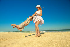 Mother twirling her son on beach. While on vacation royalty free stock images