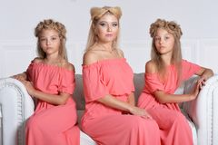 Mother with two adorable twin sisters in beautiful pink dresses. Posing together stock images