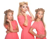 Mother with two adorable twin sisters in beautiful pink dresses stock images