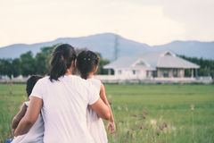 Mother and two asian little child girls looking at house. Mother and two asian little child girls looking at beautiful house in the field together in vintage royalty free stock images