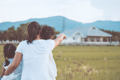 Mother and two asian little child girls looking at house Stock Images