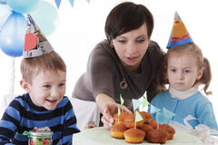Mother and two baby having birthday party in blue decor Stock Images