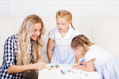 Mother with two beautiful daughters are drawing. Family, motherh Stock Image