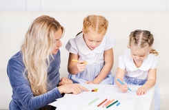Mother with two beautiful daughters are drawing. Family, motherh Royalty Free Stock Photography