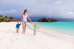 Mother and two boys walking on tropical beach Royalty Free Stock Photo