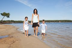 Mother and two chil son and daughter walking on the beach. And looking at the sea stock image