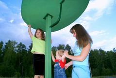 Mother with two children. The woman with the boy and the girl play in the evening a children's playground in the summer Stock Photos