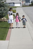 Mother and two children. A woman and her two children walking on the sidewalk Royalty Free Stock Image