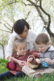 Mother and two children in blooming garden with Easter decor ele Royalty Free Stock Images