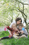 Mother and two children in blooming garden with Easter eggs Stock Image