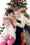 Mother and two children decorating Christmas tree Stock Photography