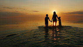 Mother with two children go swimming in the sea at sunset. Laughing stock video