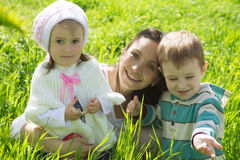 Mother with two children among green grass Stock Photography
