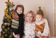 Mother and two children having fun at Christmas time. Mother and two children having fun over Christmas tree Royalty Free Stock Photos