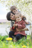 Mother and two children hugging among blooming garden Stock Photos
