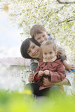 Mother and two children hugging among blooming garden Royalty Free Stock Image