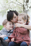 Mother and two children hugging among blooming garden Stock Image