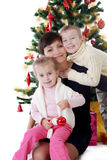 Mother and two children hugging under Christmas tree Royalty Free Stock Photo