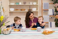Mother and two children in the kitchen. Happy mother feeds her son. Mother and son having breakfast. Concept of happy family and healthy food. Boy eating Royalty Free Stock Photos