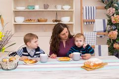 Mother and two children in the kitchen having breakfast. Happy mother feeds her son. Mother and son having breakfast. Concept of happy family and healthy food Stock Images