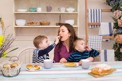 Mother and two children in the kitchen having breakfast. Happy son feeds feeds his mom. Mother and son having breakfast. Concept of happy family and healthy Royalty Free Stock Photography