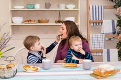 Mother and two children in the kitchen having breakfast. Happy son feeds feeds his mom. Mother and son having breakfast. Concept of happy family and healthy Stock Photo