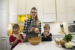 Mother and two children knead dough Royalty Free Stock Photo