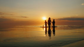 Mother with two children laughing in the sea at sunset. Out of the water stock footage