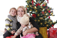 Mother with two children lookig up under Christmas tree Stock Photos