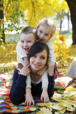 Mother and two children lying under autumn trees Royalty Free Stock Photo