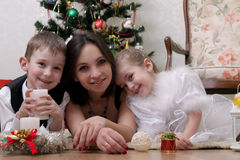 Mother and two children lying under Christmas tree Stock Photo