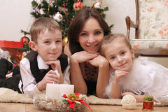 Mother and two children lying under Christmas tree. Lovely mother and two children lying under Christmas tree Stock Photos