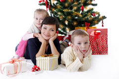 Mother and two children lying under Christmas tree with presents. Happy mother and two children lying under Christmas tree with presents isolated on white Royalty Free Stock Images