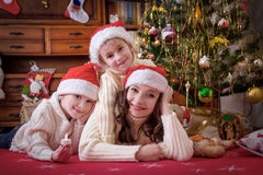 Mother and two children lying under Christmas tree Stock Photos