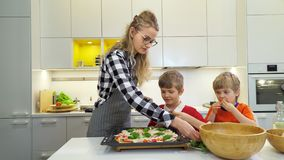 Mother and two children making pizza together stock footage