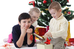 Mother and two children openning presents Royalty Free Stock Images