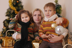 Mother and two children over Christmas tree Stock Photo
