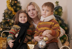 Mother and two children over Christmas tree Stock Image