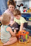 Mother and two children in playroom Stock Photos