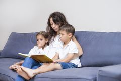 Mother with Two Children Reading a Book Together. Family Concepts. Mother with Two Children Reading a Book Together on Couch Indoors.Horizontal Image Composition Stock Images