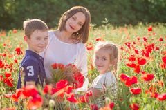 Mother with two children among red poppy field Royalty Free Stock Photo