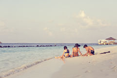 Mother with two children  relaxes on a beach Stock Photos