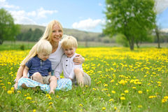 Mother and Two Children Relaxing in Flower Meadow Stock Image