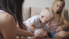 Mother and two children saving money to piggy bank. Family earning money for future. Investment concept. stock video
